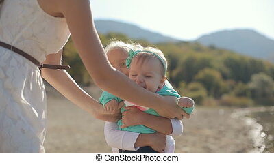 Mom gives the baby in his arms of eldest daughter