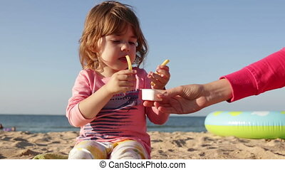 Mom gives the girl french fry and sauce. girl sitting on the sand on the beach against the sea.