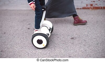 mom goes with her son, son rides next to a Gyro Scooter