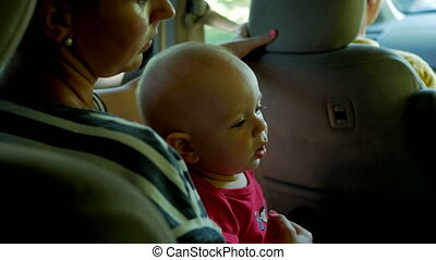 Mom goes with the kid in the back seat of the car. Cute little boy 1 year old goes to his mother's lap and looks around