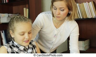 Mom helping her daughter do homework. schoolgirl makes lessons