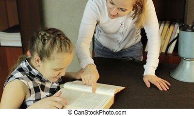 Mom helping her daughter do homework. schoolgirl makes lessons