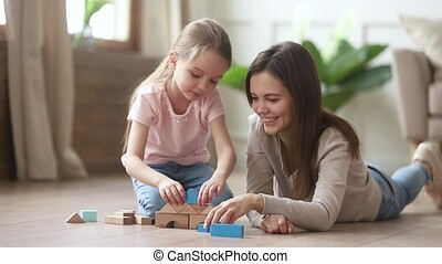 Mom helping kid daughter playing building castle from wooden...