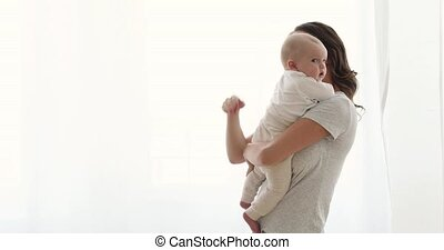 Mom holds a baby in the arms window background