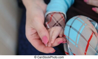 Mom holds the baby's hand