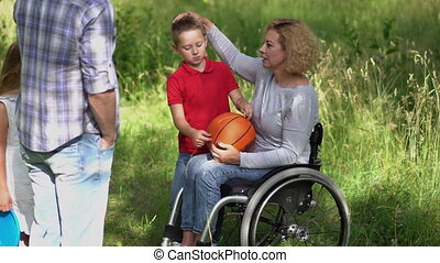 Mom in a wheelchair throws frisbee to his son and father plays with his daughter throwing a ball on nature in the park after a picnic. Family concept. Prores 422
