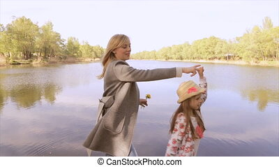 Mom in position with daughter, walk near the lake
