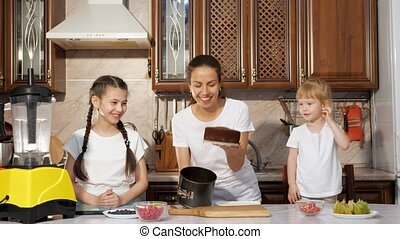 Mom is baking a cake with her two little daughters in the...