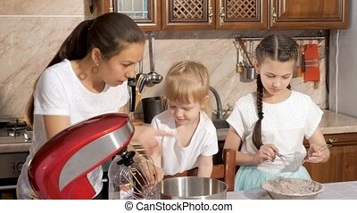 Mom is cooking with her two daughters in the kitchen.