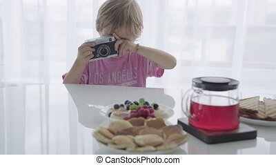 Mom is preparing Breakfast and at this time the boy plays the photographer