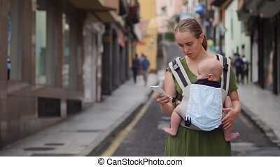 Mom is standing on the street with a baby in a sling and looks at the mobile phone screen and looks through the photos