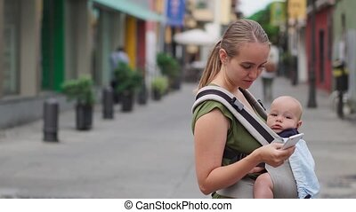 Mom is standing on the street with a baby in a sling and looks at the mobile phone screen and presses the screen with your finger