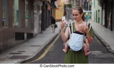 Mom is standing on the street with a baby in a sling and shoots a video for social networks about his journey to the mobile phone
