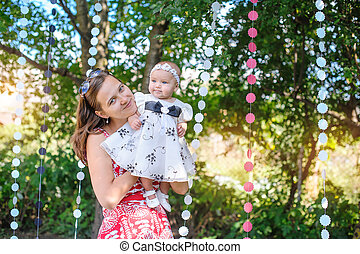 Mom keeps daughter in her arms in a beautiful dress