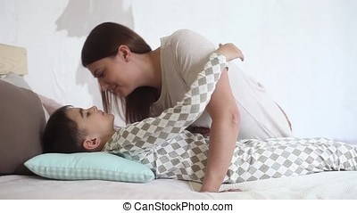Mom kisses her beloved son while he is lying on the bed and hugs her