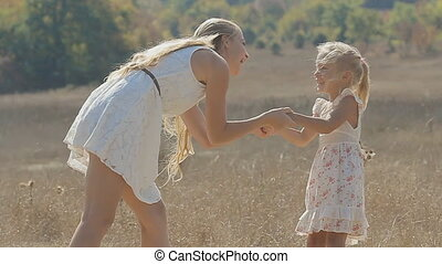 Mom kissing, hugging and laughing with her little daughter in the field in slow motion