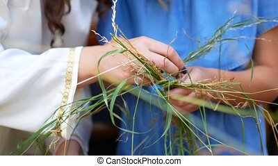 Mom learns a daughter to weave a wreath of hay