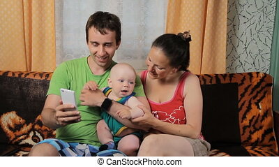 Mom, little baby and dad are doing video communication on the phone. Family sitting at home on the couch and smiling.