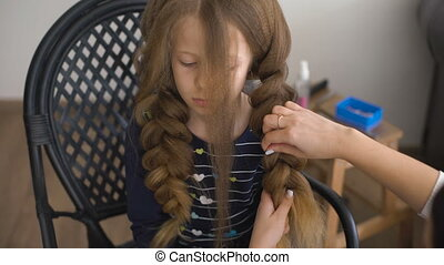 Mom makes hairstyle for a sad little girl.