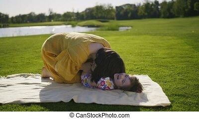 Mom making little girl daughter laugh in park