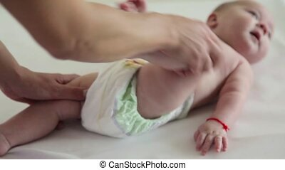 Mom massages his baby's legs with a funny face