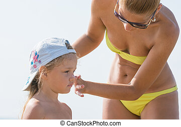 Mom misses on the beach little girl's face sunscreen