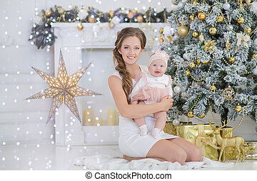 Mom mother with a little sweet and beautiful daughter spends time plays, coos, sitting next to the Christmas tree