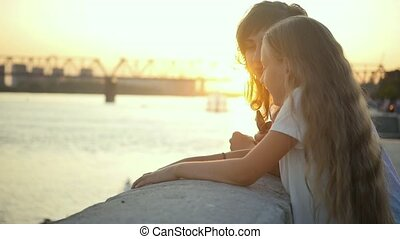 Mom next to her daughter enjoy the city sunset. Loving mom and daughter on the background of the sun setting over the horizon. Slow motion