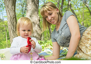 Mom on a sunny day playing with his daughter in the green park