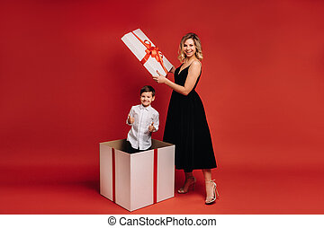 mom opens a huge Christmas gift in which a boy stands and shows the class on a red background