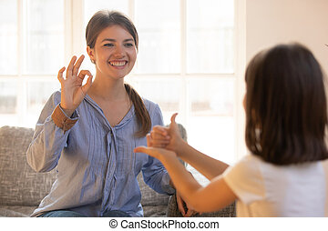 Mom or psychologist playing with child showing like ok signs