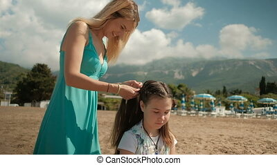 Mom plaits pigtails daughter in nature landscape outdoors....