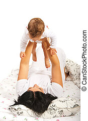 Mom playing with baby in bed