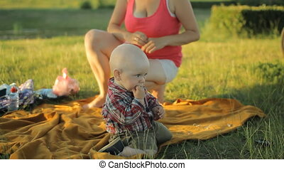 Mom playing with baby son in the park. They sit on a blanket on the grass and smiling