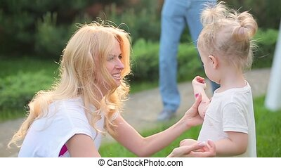 Mom plays with a daughter covered in paint