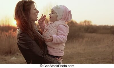 Mom plays with daughter and having fun against of sunset sky