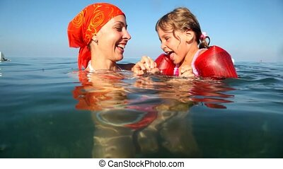 Mom plays with daughter in the water