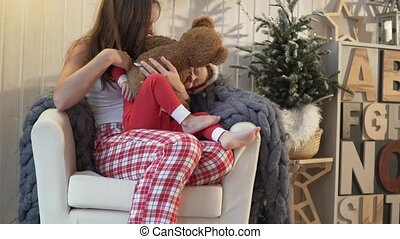Mom plays with her daughter. New Year. Girls in Christmas pajamas