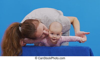 Mom plays with her newborn daughter. Isolated on blue background