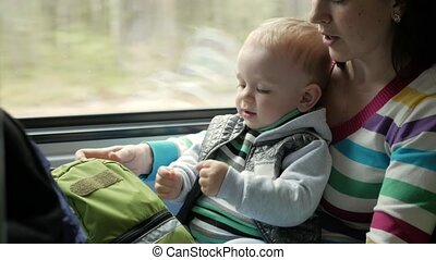 Mom plays with the baby son in a moving train near the window. The boy is on his mother's lap.