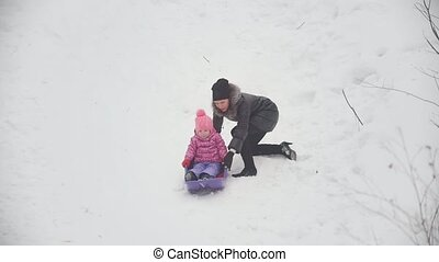Mom pulling a sled in which lying her funny daughter, winter...