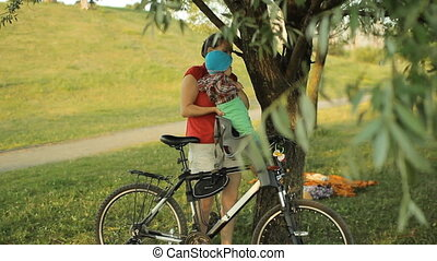 Mom pulls out a beautiful baby boy from a bicycle seat in the park