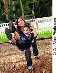 Mom pushing son on swing - Young boy swinging on swing while...