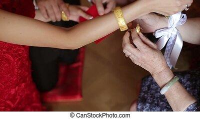 Mom put on golden bracelet to bride hand closeup