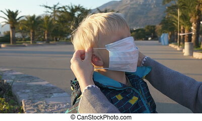 mom puts her son a medical mask on the street, portrait