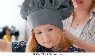 Mom puts on her daughter's chef's cap and apron, close up