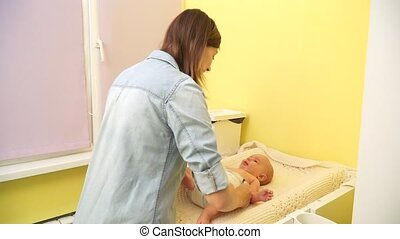 Mom puts the baby diaper