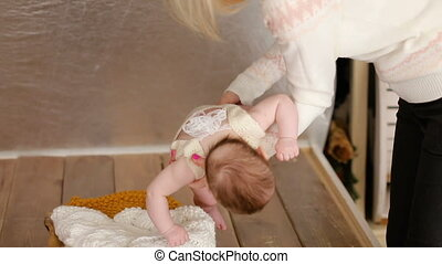 mom puts the baby in a little crib