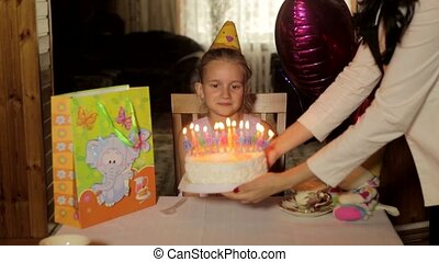Girl blows out the birthday cake at the table with gifts