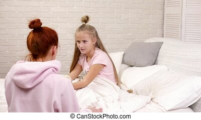 mom quarrels with child daughter in bed in the morning